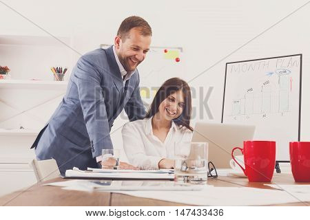 Businessman supervise and help his assistant's work on the laptop computer. Man with woman in the office. Male boss and female secretary. Communication of manager and stuff, checking job execution