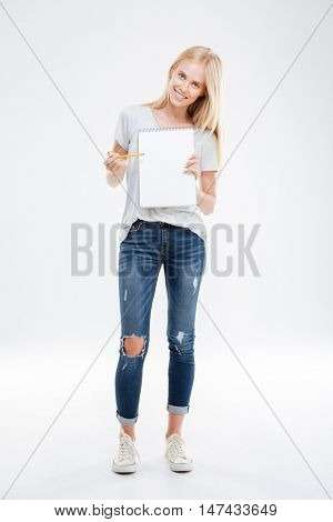 Full length portrait of a cheerful happy pretty girl pointing pencil at blank notebook isolated on the white background