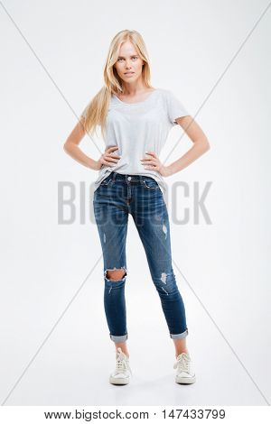 Full length portrait of a beautiful smiling girl with her arms on hips isolated on the white background