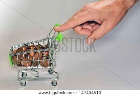 hand pushing a shopping cart full of coins