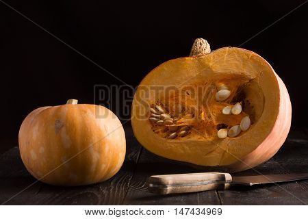 Pumpkins on the black wooden background. Horizontal orientation
