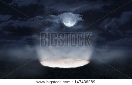 The light pouring out of a hole in the ground on the night sky background