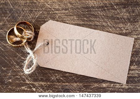 Wedding rings with blank tag on the wooden background