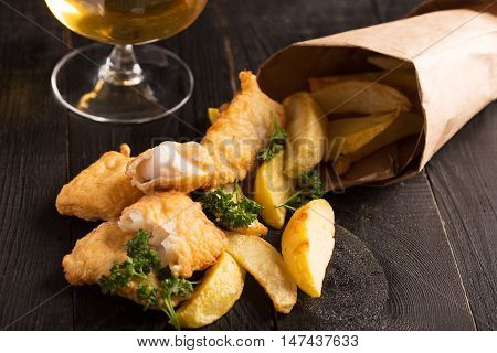 Traditional British fish and chips on the black background with glass of beer. Vertical orientation