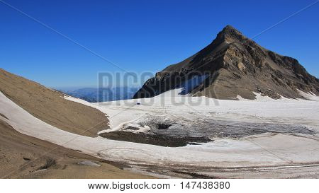 Travel destination in the Swiss Alps. Glacier de Diablerets in summer. Peak of Mt Oldenhorn. Big hole in the glacier where a temporary lake disappeared.