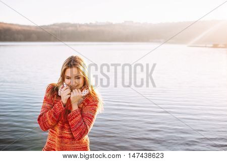 hipster shy girl wearing warm clothes standing and smiling by a lake. Sun light at sunset and copy space