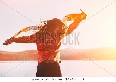 Positive young girl wearing warm winter clothes having fun at lake.
