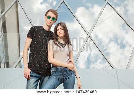 Happy Cool Looking Couple In Jeans In Front Of Office Building