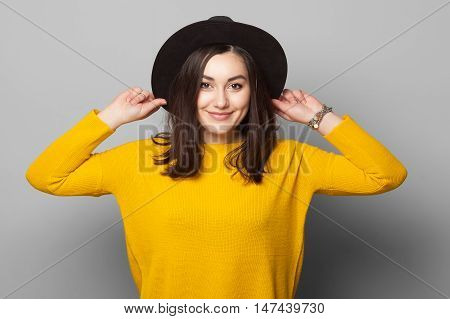Fashionable brunette wearing bright yellow clothes holding her hat with eyes closed isolated on grey background