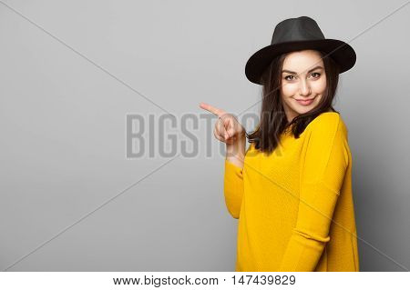 Stylish young woman pointing her finger towards blank space isolated over grey background