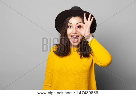 Beautiful smiling teenage girl in yellow clothes shows glasses out of fingers, against grey background