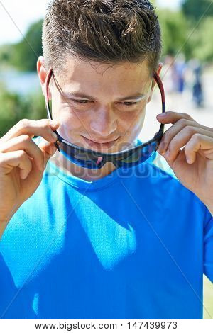 Close Up Of Young Man Running In Park Putting On Sunglasses