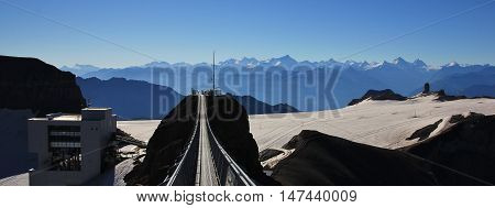 Summer morning on the Glacier de Diablerets. Suspension bridge and summit station. View from Sex Rouge. Travel destination in the Swiss Alps.