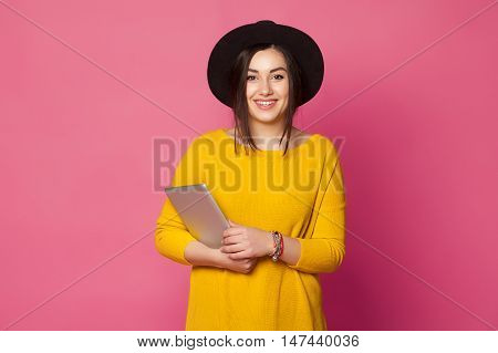 Portrait of beautiful brunette teen student holding a tablet computer and smiling isolated on pink background