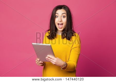 Surprised young woman wearing yellow clothes shcoked while holding tablet pc isolated on pink background