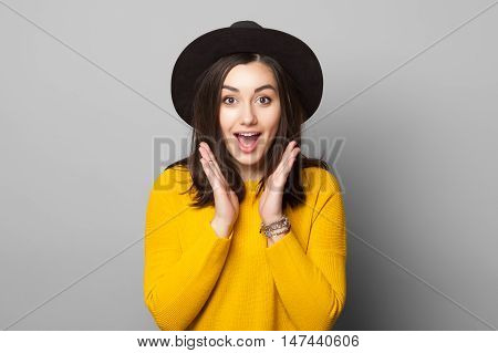 Surprised young woman wearing warm yellow clothes and stylish hat over gray background
