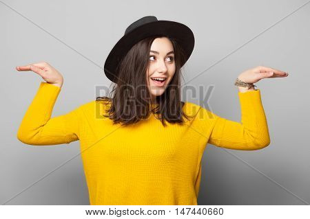 Bright trendy studio fashion image of young woman model, wearing yellow sweater, casual vintage spring style, color pop, hipster girl posing and having fun