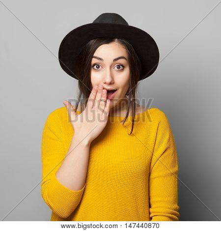 Shocked girl covers her mouth with hands, isolated on grey