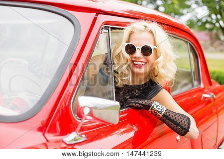 Happy woman leaning out of the car's window