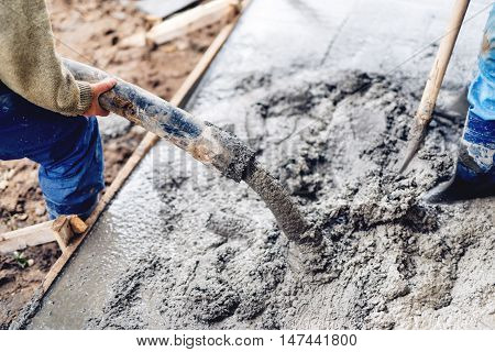 Industrial Construction Workers Using Automatic Pump Tube For Pouring Cement On Reinforcement Bars