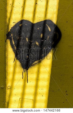 Dark heart painted on wall with spray paint. The shadows created by the sun's rays make it look like behind the bars of a prison.