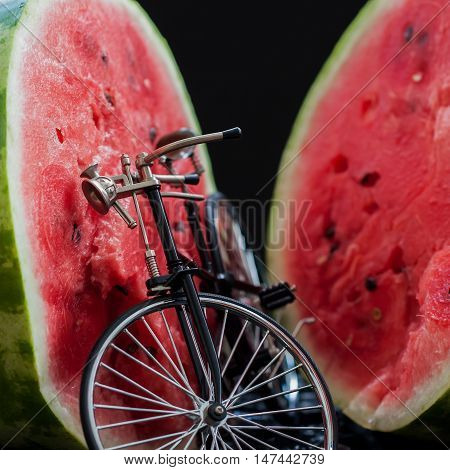 Small model of a retro vintage bicycle near a big cut in half scarlet ripe watermelon