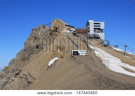 Popular travel destination in the Swiss Alps. Summit station of a cable car. Suspension bridge connecting two mountain peaks. Glacier de Diablerets in summer.