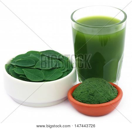 Edible moringa leaves with extract and ground paste over white background