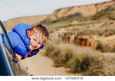 happy little boy travel by car on road to mountains, family tourism