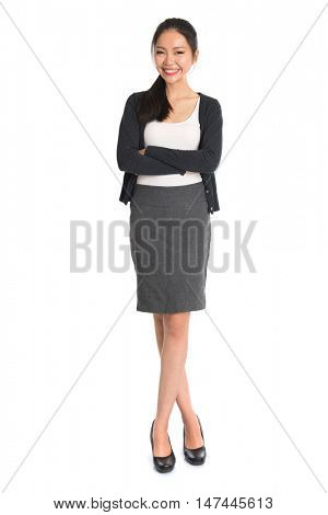 Full length portrait of young Asian girl arms crossed and smiling, standing isolated on white background.