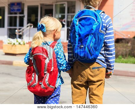 kids go to school- little boy and girl with backpacks on the street