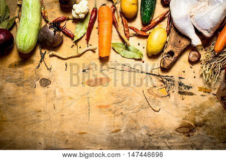 Raw chicken with vegetables and spices for soup. On a wooden table.