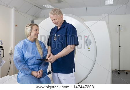 Male Doctor Showing Digital Tablet To Patient At MRI Machine