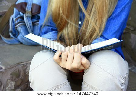 Young girl reading a book sitting on the steps of the house.