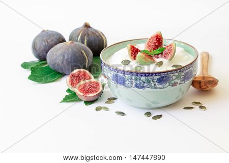 A dish of yogurt with pieces of fig fruit, near scattered sunflower seeds, laid ripe fig fruits on the fig tree leaves on the white background. Yogurt with fig fruit slices. Horizontal. Daylight.