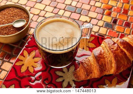 Breakfast coffee and croissant with brown sugar on red brown  tiles table