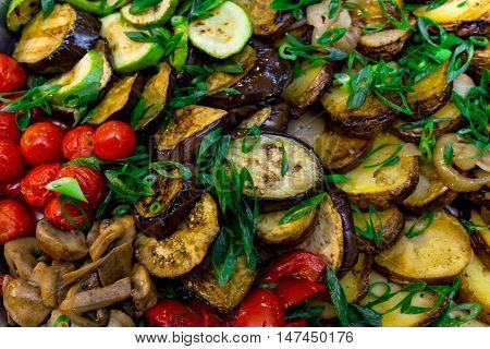 Appetizing fried vegetables with cherry tomatoes sprinkled with green onions.