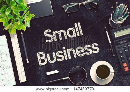 Black Chalkboard with Handwritten Business Concept - Small Business - on Black Office Desk and Other Office Supplies Around. Top View. 3d Rendering. Toned Image.