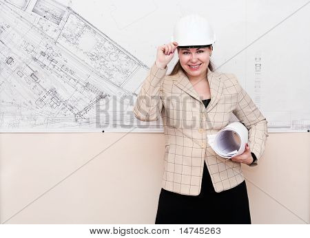 One Young Woman A Architect Standin Near The Big Blueprint On Wall And Showing
