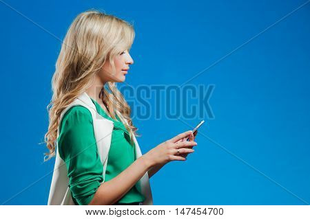 Profile of a young confident blonde, use the phone, casual style, blue background