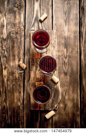 Red wine on wooden Board with stoppers and a corkscrew. On a wooden table.