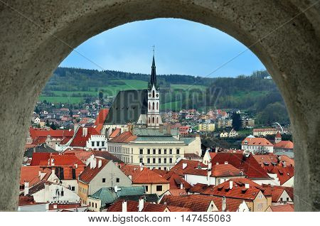 Panoramic view from arched window Cesky Krumlov Czech Republic. Red tiled roofs and Gothic church mountains in perspective.