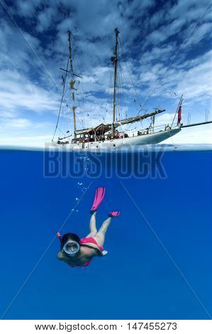 Woman snorkeling underwater a ship in background