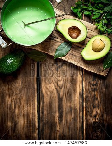 The guacamole and greens on the Board. On wooden background.