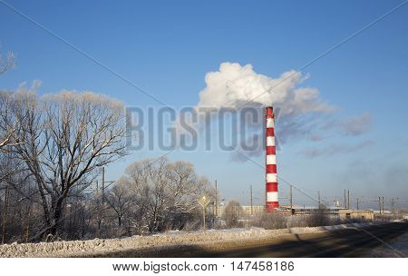 smoking chimney on a cold winter day. industrial smoke from chimney on blue sky