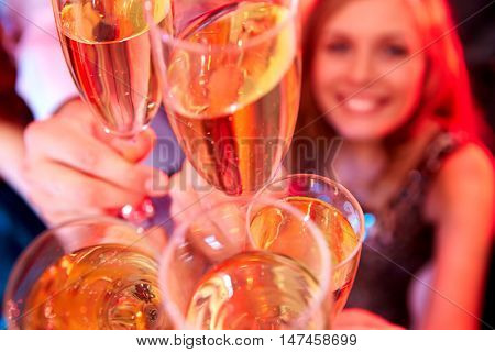 A close up of five glasses with champagne clinking above people raising them