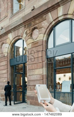 PARIS FRANCE - SEPTEMBER 16 2016: Woman in front of Apple Store looking at the New Apple iPhone 7 Plus box right after purchase on the date of worldwide launch. being tested by woman after purchase. New Apple iPhone tends to become one of the most popular