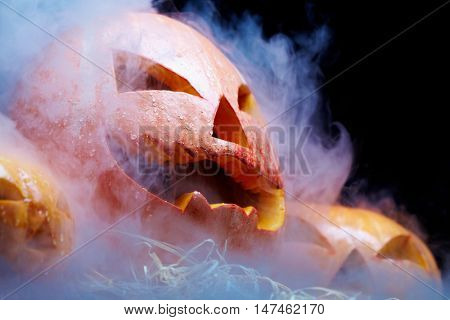 Close up of Jack O Lantern smoking among two other pumpkins against black background
