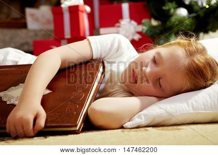 Cute little girl falling asleep with book while waiting to catch Santa Claus