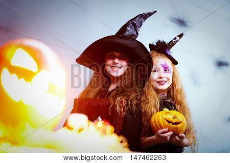 Two girls dressed in witches, one holding a book and the other with a Halloween pumpkin, looking at camera and smiling behind the flashing Jack O Lantern